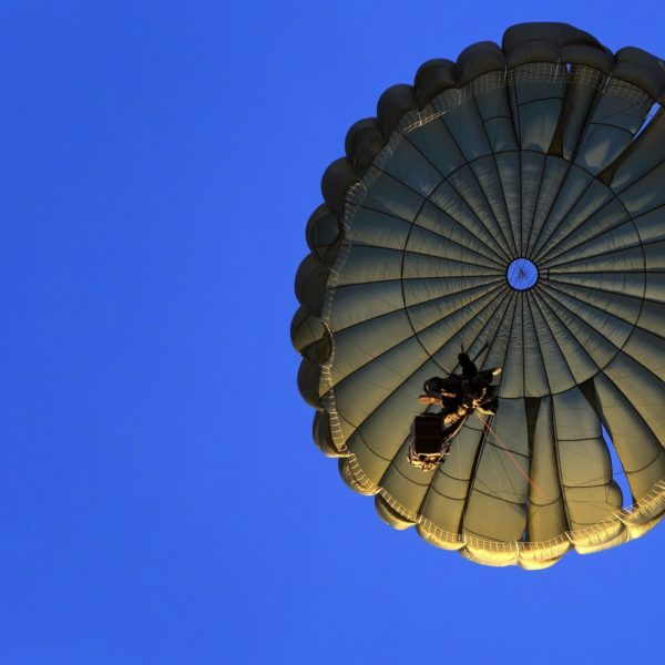 A soldier descends under a round military parachute